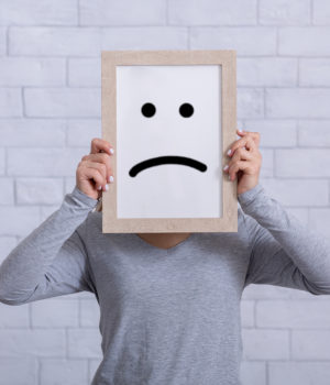 Depression, sadness, negative emotions concept. Young woman holding picture frame with sad emoticon in front of her face. Millennial lady expressing pessimism, loneliness, grief or frustration